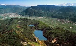 Die Montiggler Seen mit Bozen und Leifers im Hintergrund